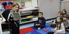 Parent volunteer reading to kindergarten students.